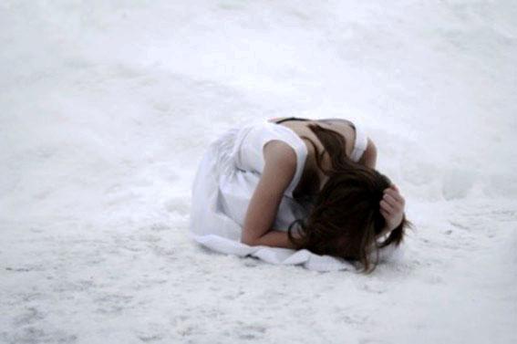 雪原で頭を抱える女性