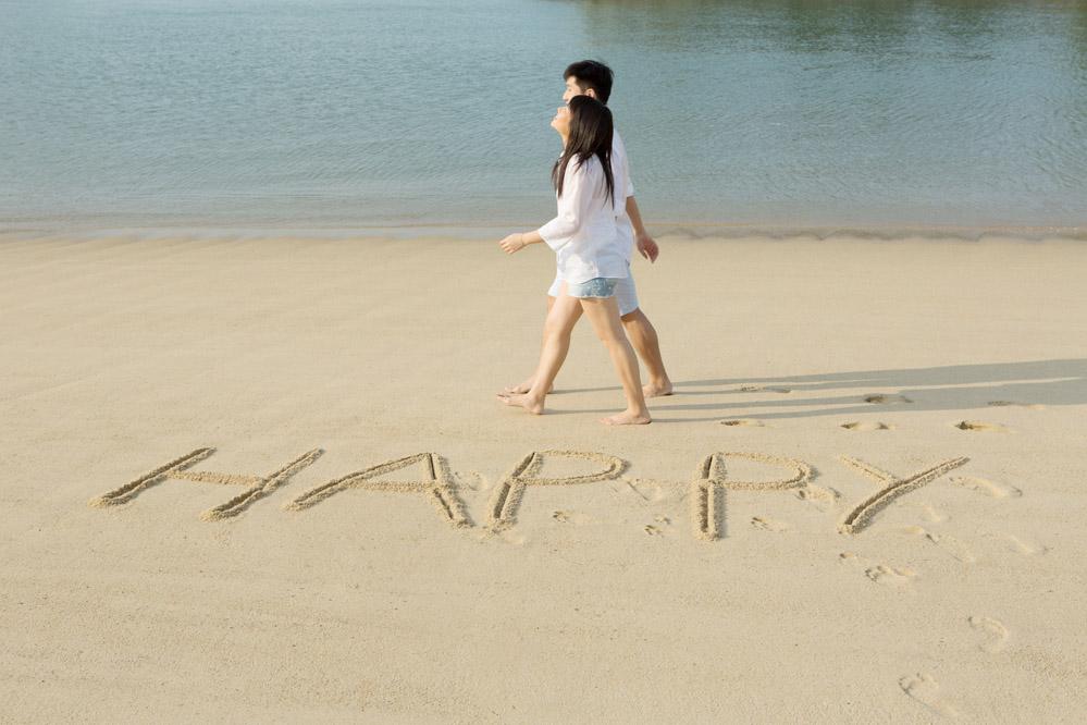 海辺をデートで散歩する若いカップル