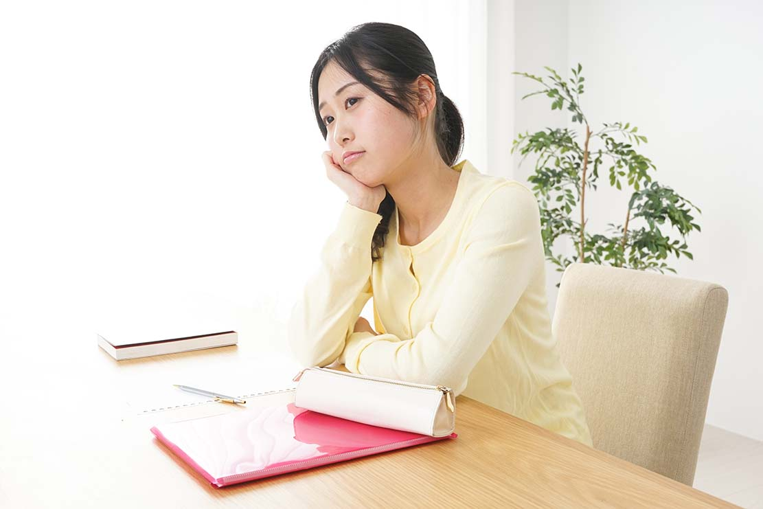 机で肘をついて悩む女性