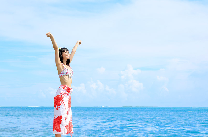 海辺で笑顔の若い女性