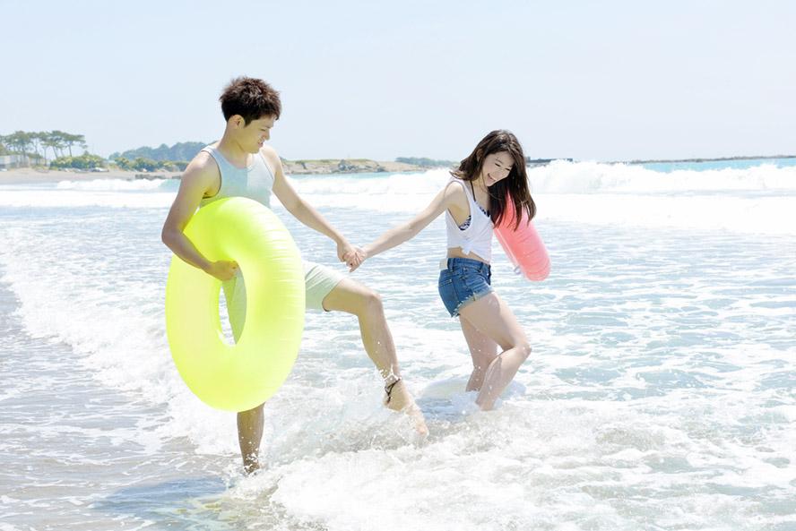 浮き輪を持って波打ち際で遊ぶカップル